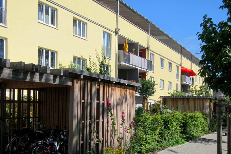 dreigeschossiges Wohnhaus mit überdachten Holzlauben für Fahrräder