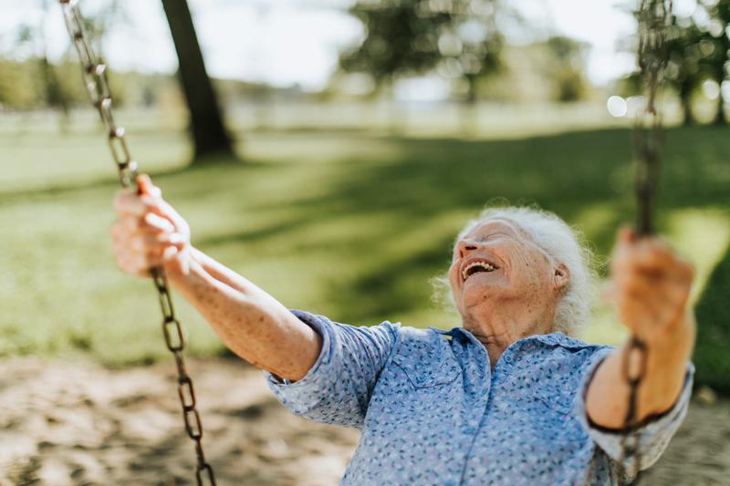 Eine alte Frau hat beim Schaukeln viel Spaß